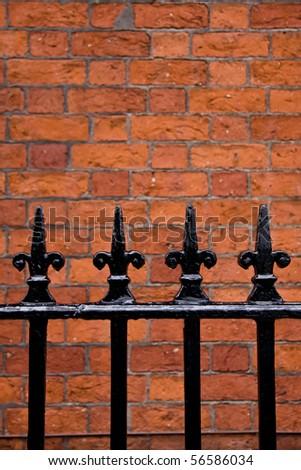 Black Railings and brick wall - stock photo