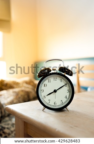 Black retro alarm clock and bed in morning light, 7.00 AM alarm clock in morning. Shallow depth of field focus on black alarm clock.