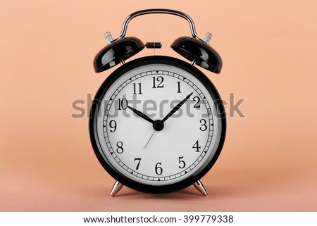 Black retro alarm clock on peach background - stock photo