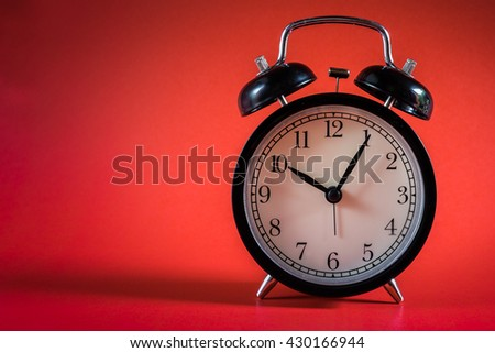 Black retro alarm clock on red background.retro clock. 10 o'clock and five minutes. clock concept. alarm clock with space for text. - stock photo