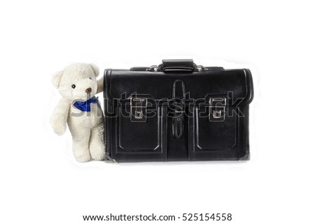 Black retro leather schoolbag with teddy bear on background