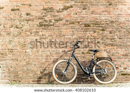 Black retro vintage bicycle with old brick wall and copy space. Retro bicycle with basket in front of the old brick wall. Old photo effect applied. Toned.  - stock photo