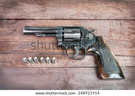 black revolver gun with bullets isolated on wooden background. - stock photo