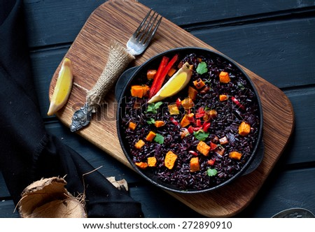 Black rice paella with pumpkin - stock photo