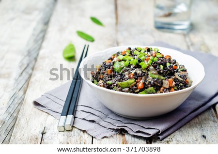 Black rice with snap peas and vegetables on a white background wood. toning. selective Focus - stock photo