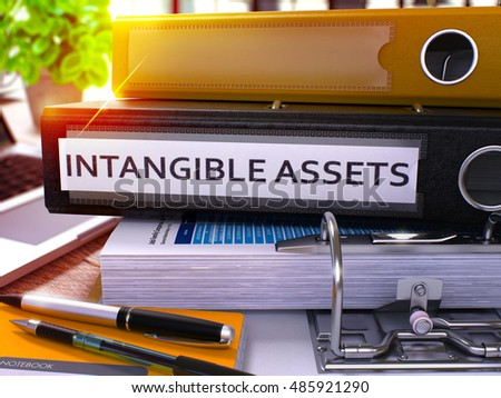 Black Ring Binder with Inscription Intangible Assets on Background of Working Table with Office Supplies and Laptop. Intangible Assets Business Concept on Blurred Background. 3D Render.