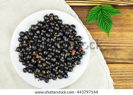 Black ripe currant in white plate on old linen canvas, wooden table, top view, flate image - stock photo