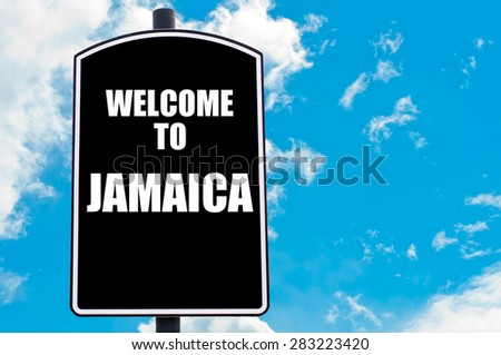 Black road sign with greeting message WELCOME TO JAMAICA isolated over clear blue sky background with available copy space. Travel destination concept  image
