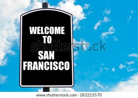 Black road sign with greeting message WELCOME TO SAN FRANCISCO isolated over clear blue sky background with available copy space. Travel destination concept  image