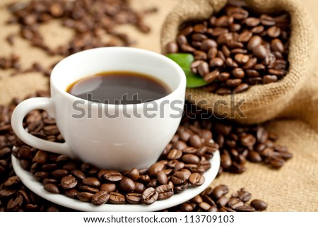 black roasted arabica coffee beans and cup full of coffee