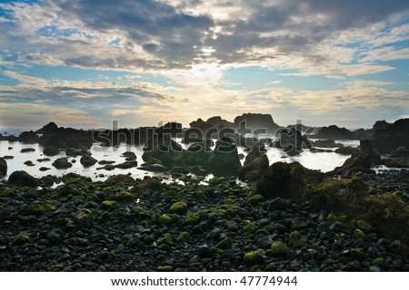 Black rocky volcanic coastline in a dramatic sunset, Pico island , Azores, Atlantic Ocean - stock photo