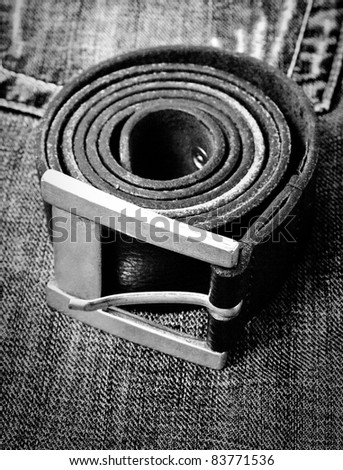 black rolled belt on jeans background - stock photo