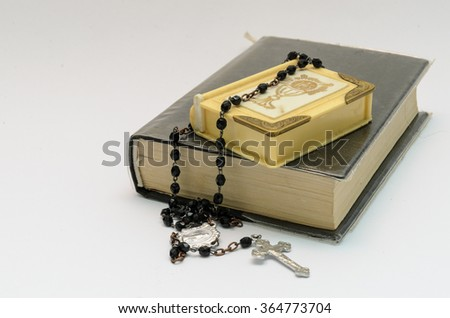 black rosary beads and black catechism on white background - stock photo