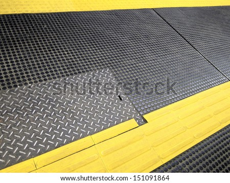 Black rubber flooring - slip - Station - subway - Yellow Stripe - warning - stock photo