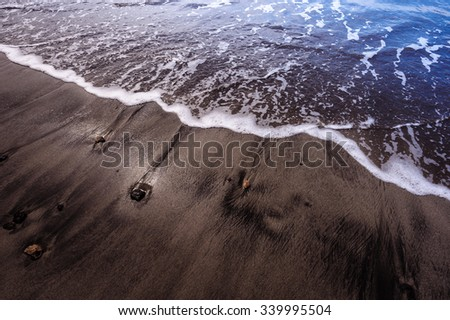Black sand beach volcanic in Tenerife at Canary Islands - stock photo