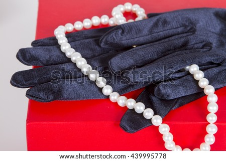 black satin gloves and pearl beads on a neck decoration on a red background. theater - stock photo