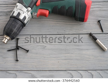 black screws, screwdriver bits, and electrical screwdriver are lying on a grey wooden board, low depth of sharpness - stock photo