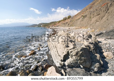 Black sea coastline with foam, transparent water, stones, pebbles and rocks against the blue sky with clouds