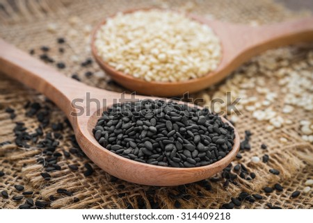 Black sesame and white sesame seed on wooden spoon - stock photo