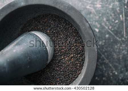 Black sesame seeds. Healthy sesame seeds in mortar. Top view. - stock photo