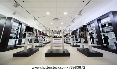 Black shelves with many boots and shoes into large shoe store - stock photo