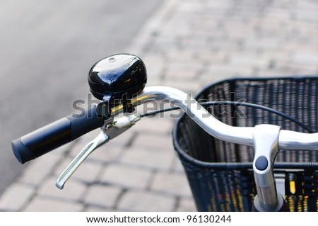 Black shiny bicycle bell and front basket - stock photo