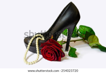 Black shoe, pearls and red rose on white background  - stock photo