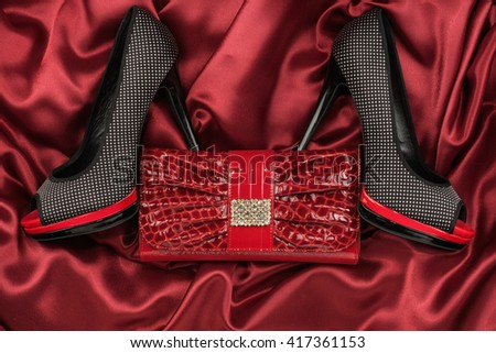 Black shoes and purse lying on the red satin, top view