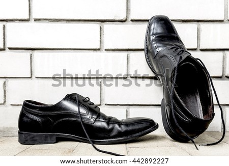 Black shoes,  footwear and brick wall background with copy space