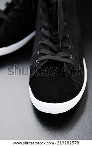 Black shoes sneakers with black laces and white rubber sole foot on black background, closeup. Selective focus. - stock photo