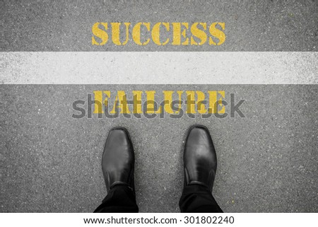 Black shoes standing at the line between failure and success