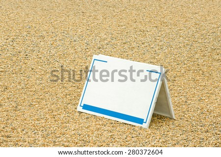 black sign template on a pebbled beach - stock photo