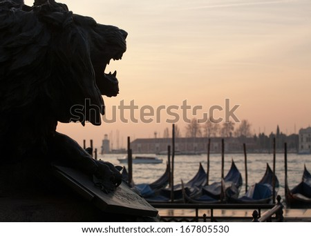 Black silhouette of lion statue head on Venice lagoon and gondolas sunset view background - stock photo