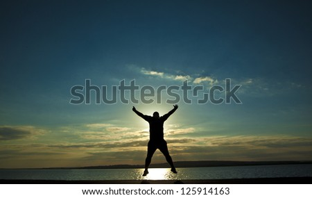 black silhouette of man in happy jump on orange sunset sky and sea
