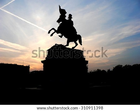 Black silhouette of monument of horse rider with flag on background of rose sunset
