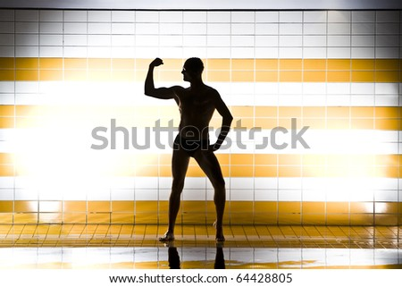 black silhouette of muscular swimmer on light background - stock photo