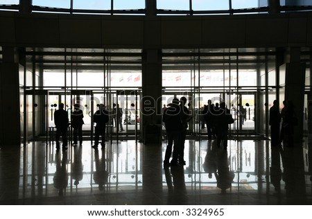 Black silhouette of people against light in an extensive passage. Back lighting. - stock photo