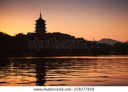 Black silhouette of traditional Chinese pagoda on orange evening sky background. Coast of West Lake. Famous park in Hangzhou city center, China - stock photo