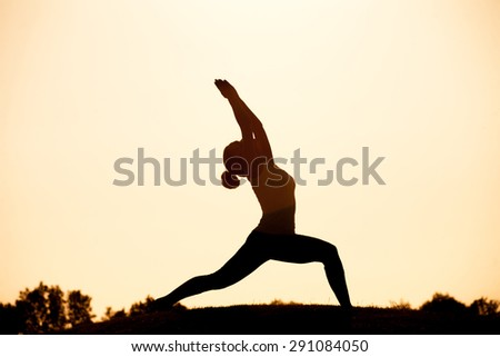 Black  silhouette of yogi girl in low lunge pose - asana pose. Beautiful woman practicing outdoors against sunset sky. - stock photo