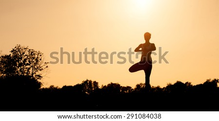 Black silhouette of yogi girl with her hands clasped on front of her chest. Beautiful girl with ideal back posture practicing. - stock photo