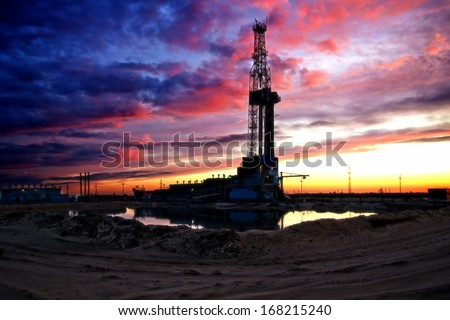 Black silhouette oil rig on dramatic sky background - stock photo