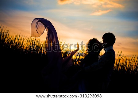 Black silhouettes of men and women against the background of a beautiful sunset, love, dating, kiss, the dress looks like a mermaid tail - stock photo