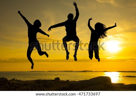 Black silhouettes of three happy friends jumping on beach in front of sunset