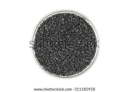 Black silicon carbide powder in a glass container on a white background