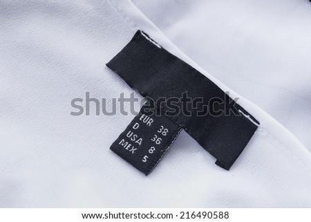 Black size label on white cloth closeup as a background - stock photo