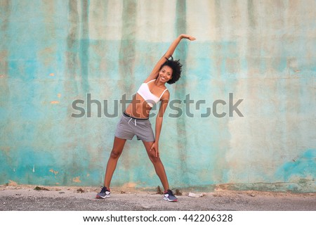 Black skin woman doing stretching in the street - stock photo