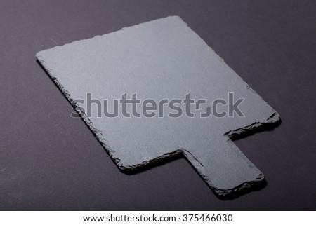 Black slate cutting board on black background. Selective focus. - stock photo