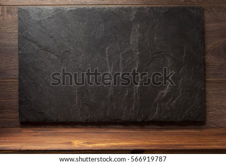 black slate stone on wooden background