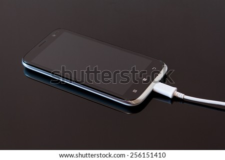 Black Smart Phone Charging with Cable on the Black Table - stock photo