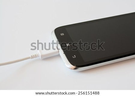 Black Smart Phone Charging with Cable on the white Table - stock photo